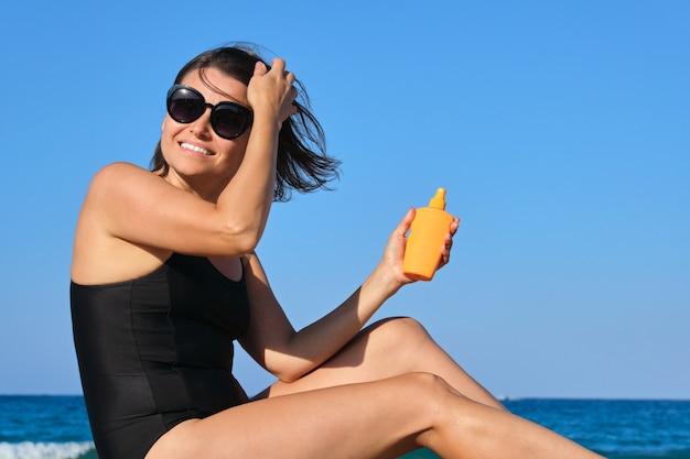 Mulher madura bonita sentada na praia usando creme de proteção solar