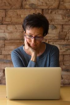 Mulher madura bonita usando laptop, usando óculos e apoiando o queixo na mão