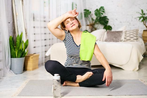 Mulher madura caucasiana após o exercício está descansando sentado em uma esteira em casa em um quarto com uma toalha aro ...