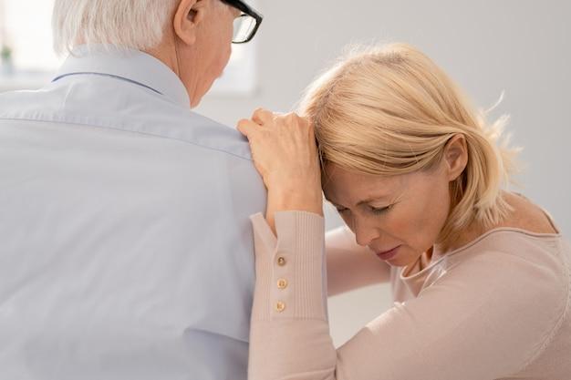 Mulher madura chateada e de luto, colocando a cabeça e as mãos no ombro de um colega de grupo idoso enquanto compartilha seu problema