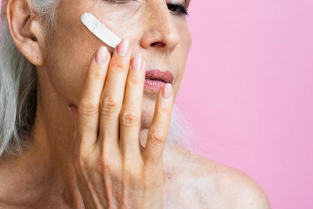 Mulher madura close-up com creme hidratante