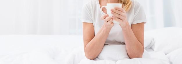 Mulher madura close-up, desfrutando de uma xícara de café