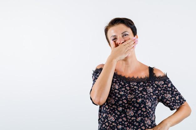 Mulher madura cobrindo a boca com a mão, segurando a mão na cintura em uma blusa floral, saia preta e parecendo feliz. vista frontal. Foto gratuita