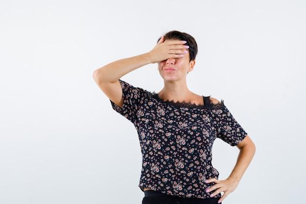 Mulher madura cobrindo os olhos com a mão, segurando a mão na cintura em uma blusa floral, saia preta e olhando alegre, vista frontal.