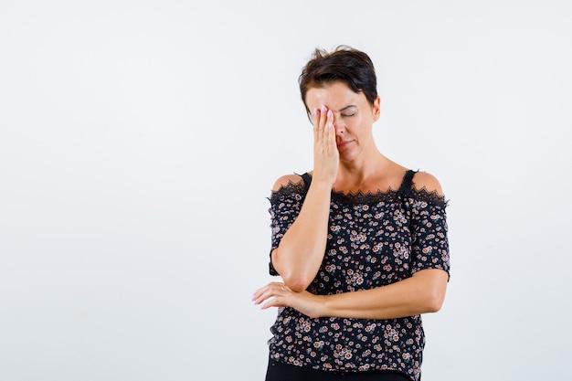 Mulher madura cobrindo um olho com a mão, segurando a mão sob o cotovelo em uma blusa floral, saia preta e parecendo exausta. vista frontal.