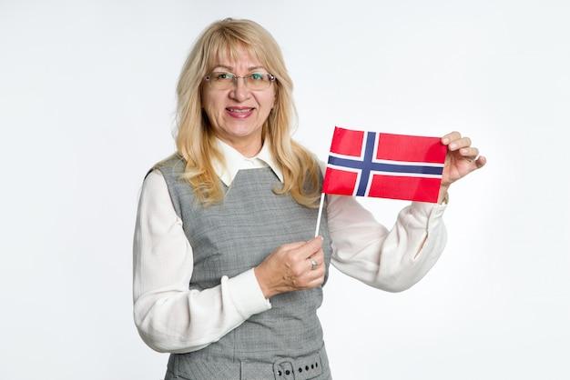 Mulher madura com bandeira da noruega no fundo brilhante.