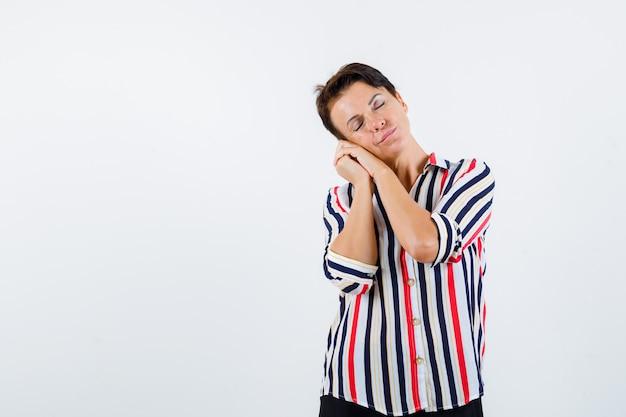 Mulher madura com blusa listrada, apoiando a bochecha nas palmas das mãos como travesseiro, fechando os olhos e parecendo com sono, vista frontal.