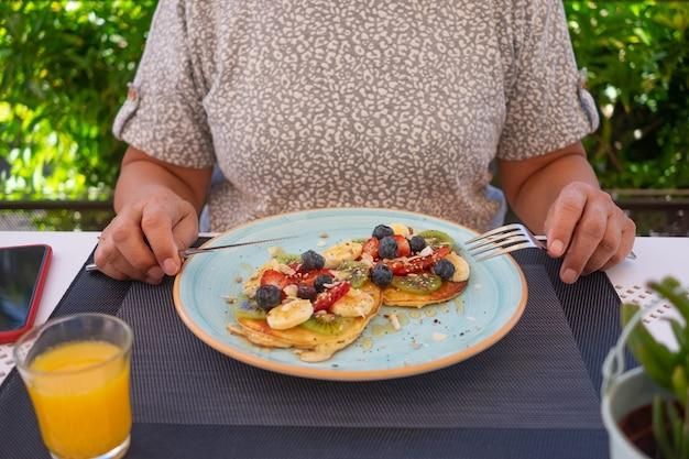 Mulher madura com café da manhã saudável de verão, panquecas americanas clássicas com banana, kiwi, frutas frescas e mel