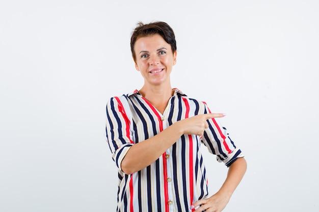 Mulher madura com camisa listrada, apontando para a direita com o dedo indicador, segurando a mão na cintura e parecendo feliz, vista frontal.