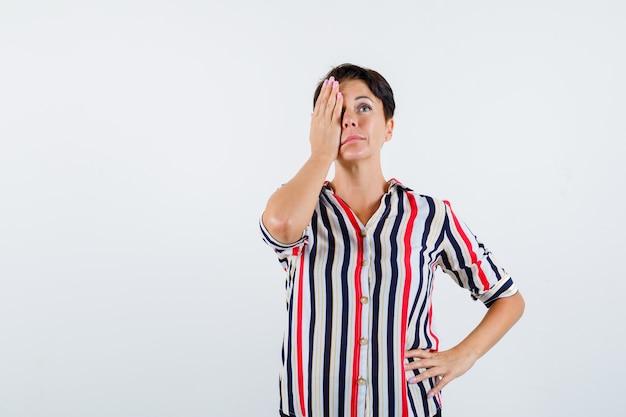 Mulher madura com camisa listrada, cobrindo os olhos com a mão, segurando a mão na cintura e olhando séria, vista frontal.