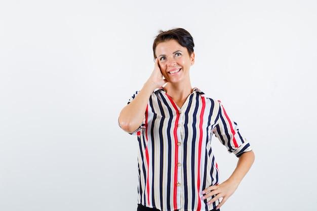 Mulher madura com camisa listrada, inclinando a bochecha na palma da mão, segurando a mão na cintura e olhando encantadora, vista frontal.