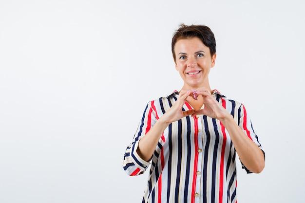 Mulher madura com camisa listrada, mostrando um gesto de amor com as mãos e olhando feliz, vista frontal.