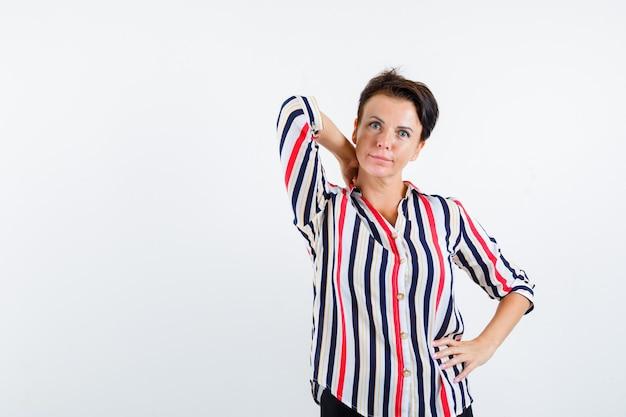 Mulher madura com camisa listrada, segurando a mão no pescoço e olhando pensativa, vista frontal.