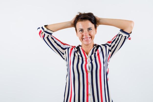 Mulher madura com camisa listrada, segurando as mãos na cabeça e olhando feliz, vista frontal.