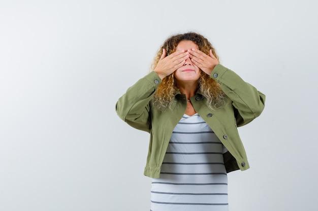 Mulher madura com casaco verde, t-shirt cobrindo os olhos com as mãos e parecendo envergonhado, vista frontal.