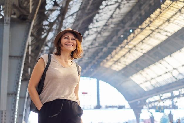 Mulher madura com chapéu com mochila mala andando na plataforma da estação ferroviária. turismo, viagens, viagem, transporte, conceito de pessoas de meia-idade, espaço de cópia