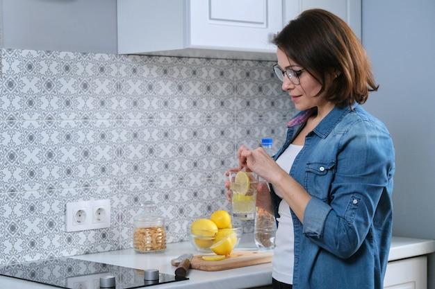 Mulher madura com copo de água com limão na cozinha, antioxidante natural