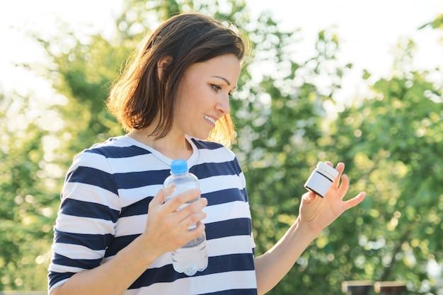 Mulher madura com frascos de remédios, vitaminas, suplementos