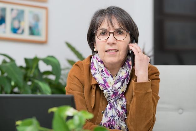 Mulher madura com jaqueta marrom falando no telefone em casa