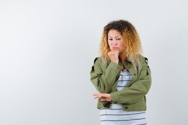 Mulher madura com jaqueta verde, camiseta mantendo o punho no queixo, olhando para baixo e olhando pensativa, vista frontal.