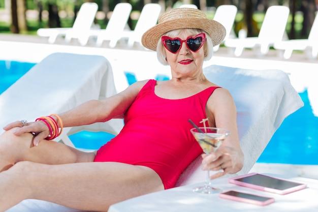 Mulher madura com lábios vermelhos brilhantes bebendo martini gelado enquanto se bronzeava deitada perto da piscina