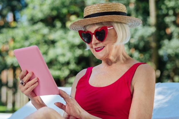 Mulher madura com lábios vermelhos se sentindo descansada enquanto lê um livro eletrônico em seu laptop rosa