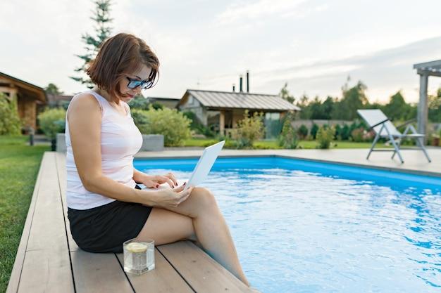 Mulher madura com laptop perto de piscina particular