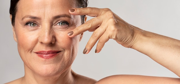 Mulher madura com maquiagem, posando com a mão no rosto e mostrando as unhas