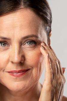Mulher madura com maquiagem posando com a mão no rosto