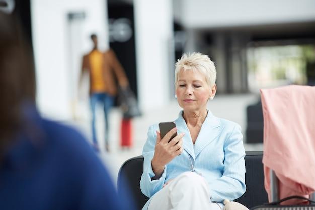 Mulher madura com maquiagem sentado no aeroporto