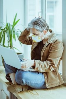 Mulher madura com máscara fp1 estudando informações com entusiasmo, olhando para um laptop sentado no parapeito de uma janela