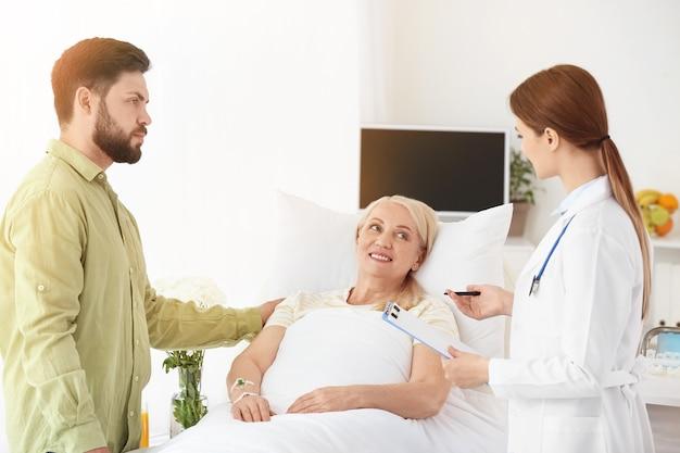 Mulher madura com médico e filho em quarto de hospital