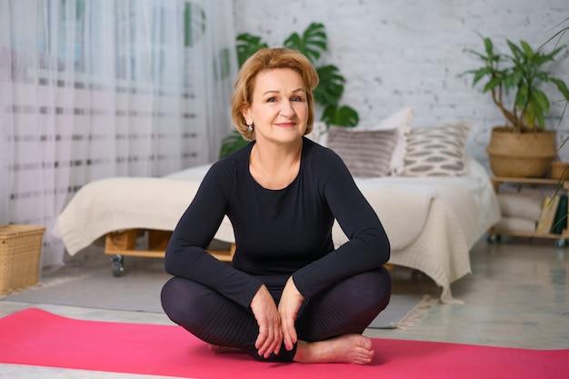 Mulher madura com um agasalho esportivo preto fazendo ioga, sentada no tapete em casa