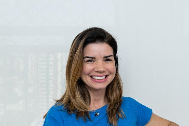 Mulher madura com um grande sorriso, camisa azul e cortina lisa ao fundo