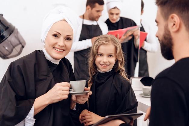 Mulher madura com xícara de café e menina curly no salão de beleza.