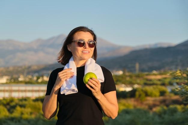 Mulher madura comendo maçã após correr
