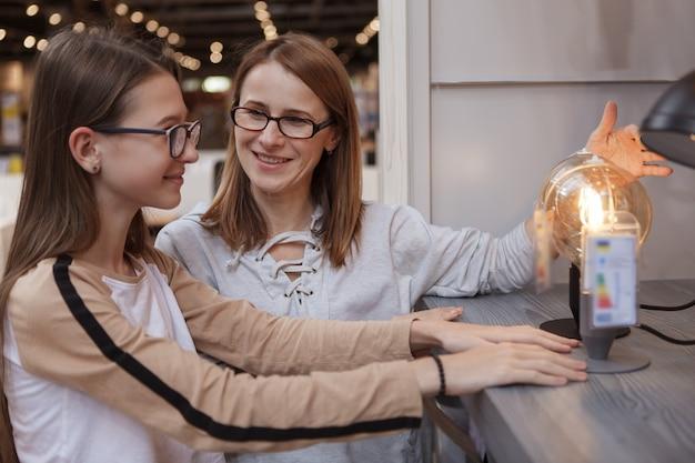Mulher madura comprando produtos para a casa com a filha adolescente em uma loja de móveis
