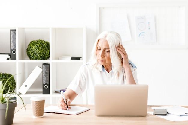 Mulher madura concentrada com laptop