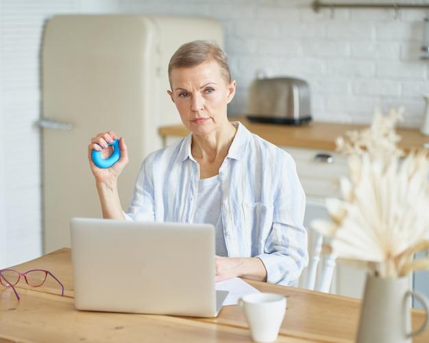 Mulher madura concentrada se exercitando com anel de borracha para as palmas das mãos enquanto trabalha em casa