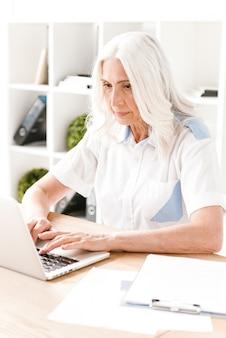 Mulher madura concentrada sentada trabalhando