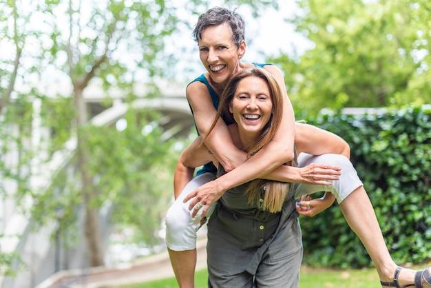 Mulher madura dando carona para uma amiga madura feminina no parque. amigos de meia idade compartilhando tempo juntos e se divertindo.
