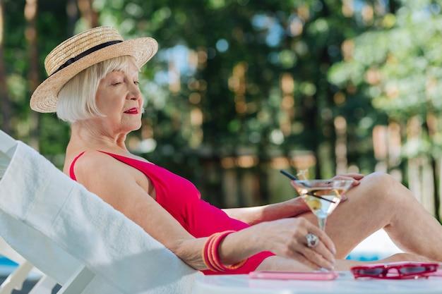 Mulher madura de cabelo loiro com lábios vermelhos brilhantes e chapéu de palha deitada perto da piscina