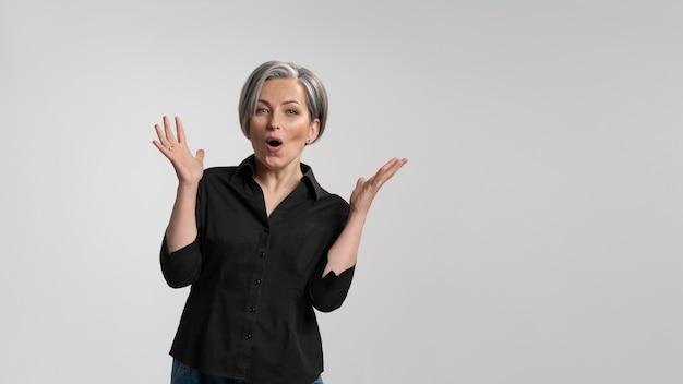 Mulher madura de cabelos grisalhos fazendo um gesto de espanto. mulher bonita de cabelos grisalhos de meia-idade em camisa preta