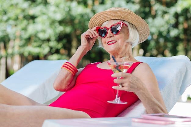 Mulher madura de cabelos loiros se sentindo extremamente feliz enquanto descansa perto da piscina