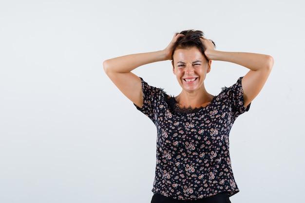 Mulher madura de mãos dadas na cabeça, sorrindo em blusa floral, saia preta e parecendo feliz. vista frontal.