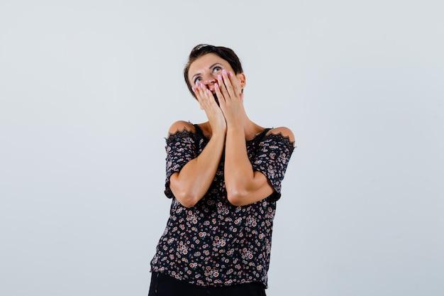Mulher madura de mãos dadas nas bochechas enquanto olha para cima na blusa e olhando espantada, vista frontal.