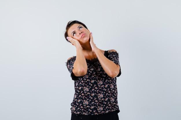 Mulher madura de mãos dadas nas bochechas enquanto olha para cima na blusa e olhando pensativa, vista frontal.