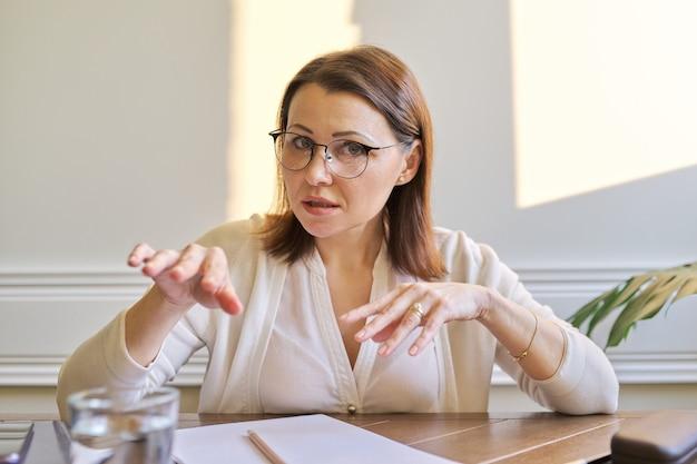 Mulher madura de negócios assistindo webcam e dando videoconferência