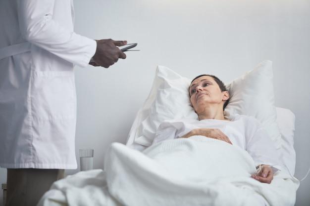 Mulher madura deitada na cama e falando com o médico no hospital