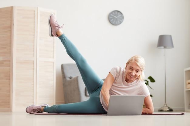Mulher madura deitada no chão na esteira de exercícios e esticando a perna enquanto observa o treinamento esportivo no laptop em casa
